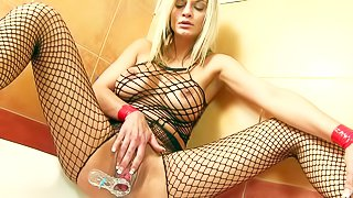 Big breasted blonde Klarisa in black crotchless fishnet body stocking spreads her legs and shows her cunt before pissing and playing with sex toy in the bedroom